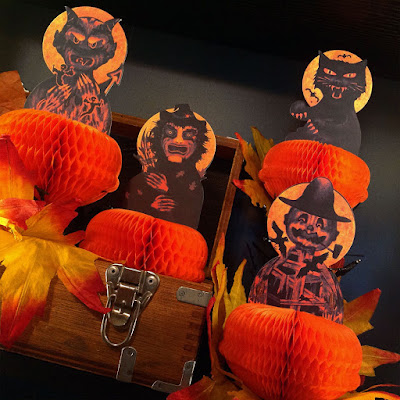 Four characters - black cat, scarecrow, witch, and devil with honeycomb tissue paper on the shelf with leaves and an old crate.
