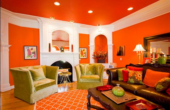 Una sala con paredes en color naranja donde el color blanco pone la