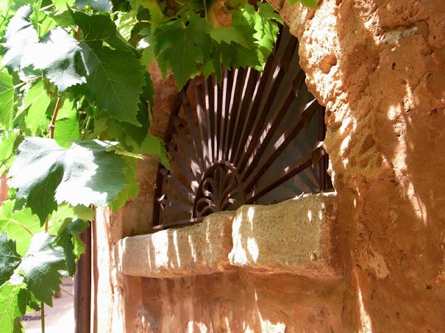 Halbrundes Eisengitter vor Fenster, die Sonne kann nicht ganz drauf scheinen, da das Fenster von einem Baum verdeckt wird