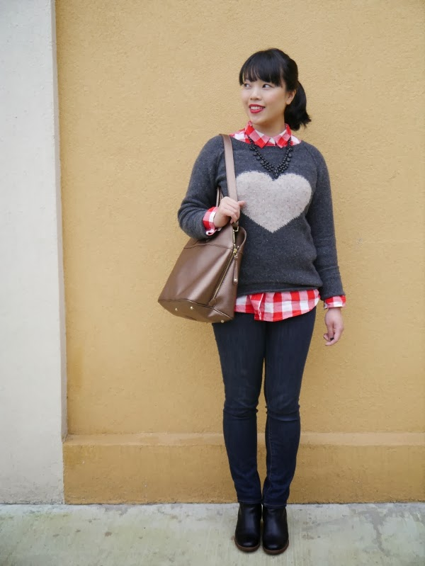 Charcoal grey heart intarsia sweater layered over red check shirt and black matte statement necklace. Skinny dark blue jeans, black ankle boots, red lipstick, gold saffiano leather bag.
