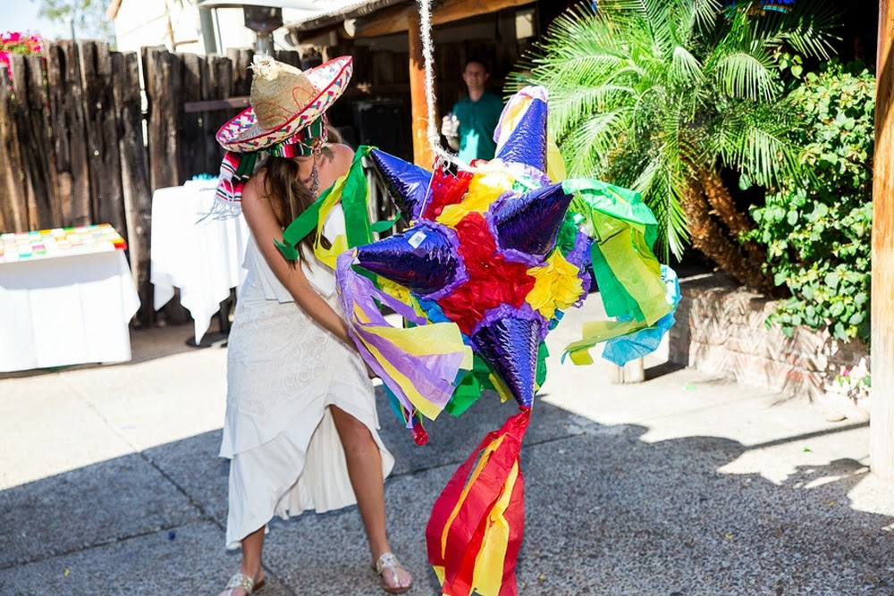 bride hitting pinata, festive mexican themed wedding, aunt chiladas