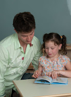montessori teacher and girl reading state standards montessori method blended combination public schools
