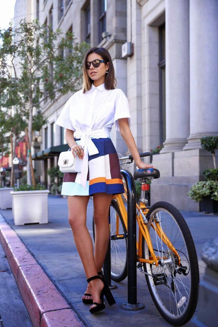 Blusa branca com mini-saia padrão geométrico, pumps e clutch pretas