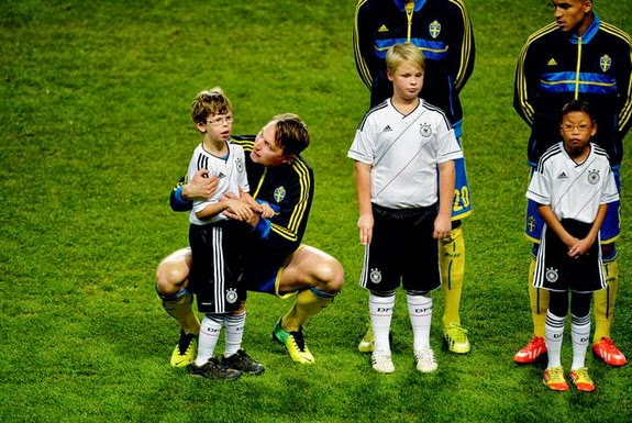Sweden player Kim Källström speaks with one of the mascots prior to a match against Germany