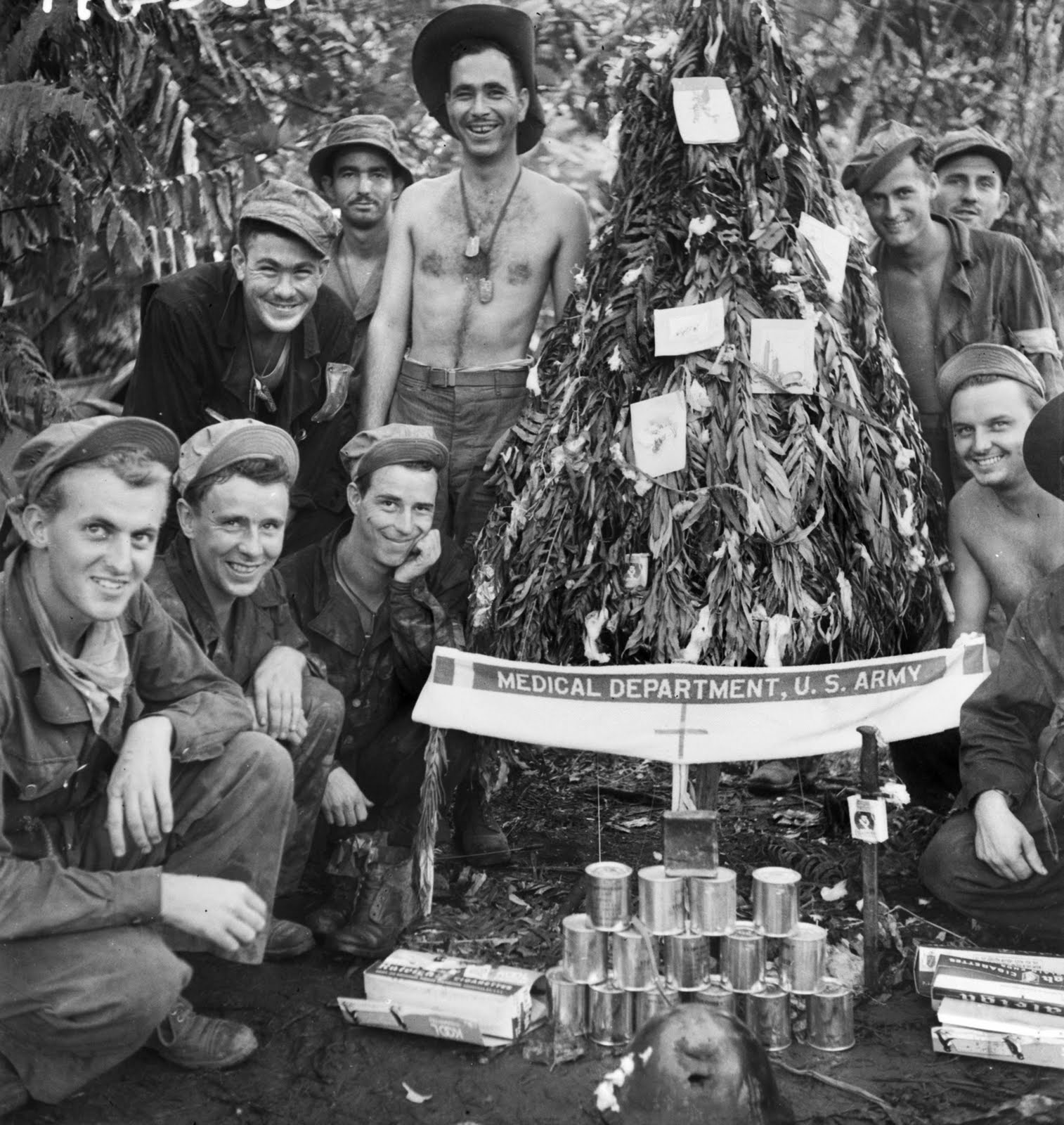 wwii soldiers decorating a palm tree for christmas