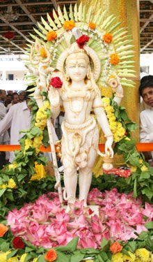 A white murti of Lord Shiva adorned with and surrounded by flowers