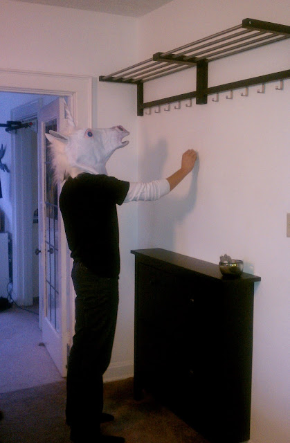 A man in a unicorn mask helps hang IKEA Tjusig coat racks above a Hemnes shoe cabinet