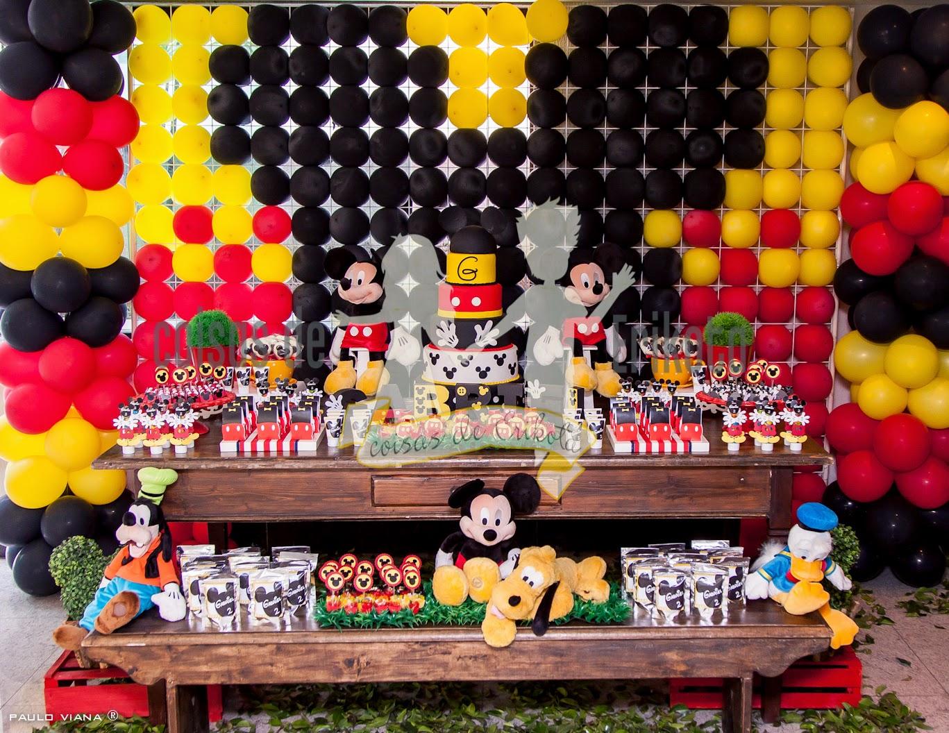 mesa de festa personalizada com bolo, doces e bonecos em pelúcia do mickey.Atrás da mesa tem uma tela de balões.