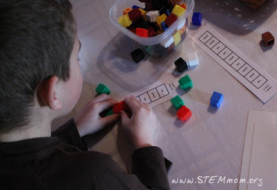 Boy using cubes to show he knows his color words: STEMmom.org