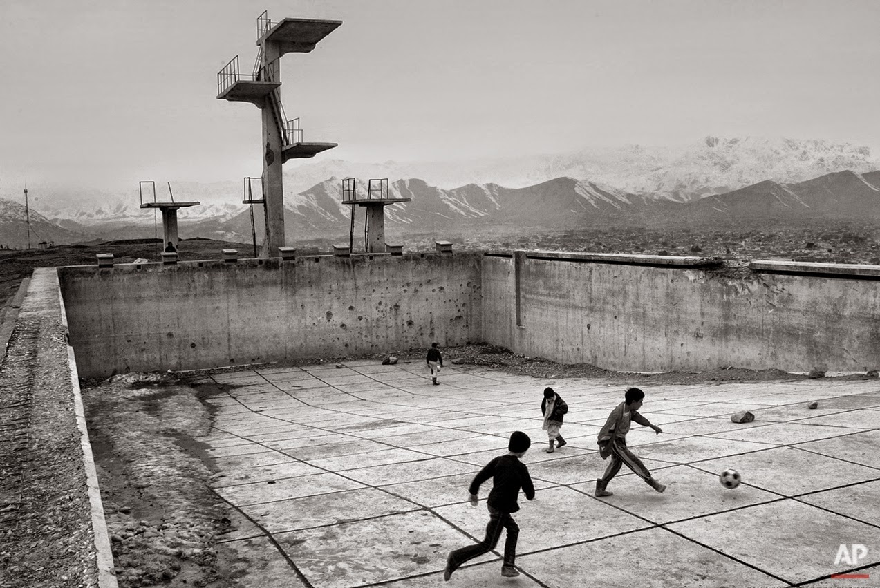 Soccer in an empty and war-damaged Soviet occupation-era swimming pool