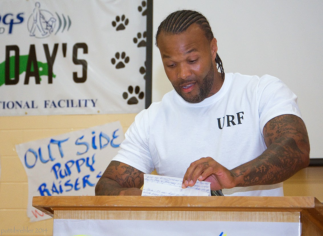 An african american man with corn-rows and a light beard wearing a white t-shirt is standing behind the podium reading from a piece of paper that he is holding with his left hand. His arms are covered with tatoos.
