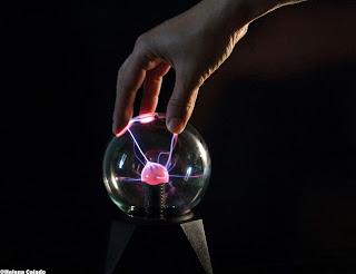 fotografia do efeito da mão humana na bola de plasma