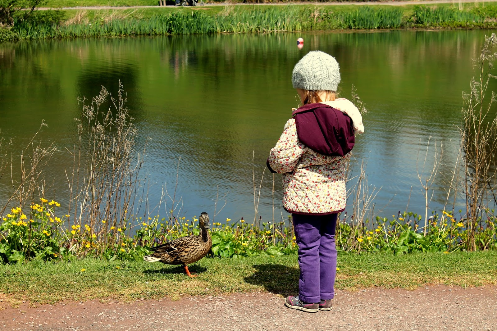 girl standing with duck at lake