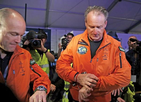Hai phi công Andre Borschberg (phải) và Bertrand Piccard kiểm tra giờ trước khi xuất phát từ sân bay Abu Dhabi