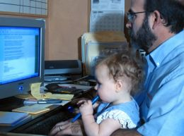 baby in dad's lap while he works at computer