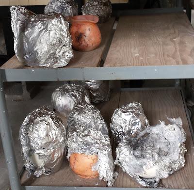 Ceramic pots coming out of the foil saggar raku firing.