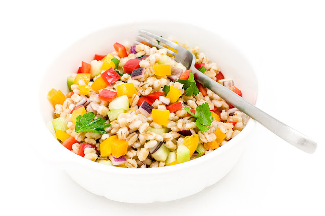 Cold pot barley salad peppers onion cucumber parsley in a bowl