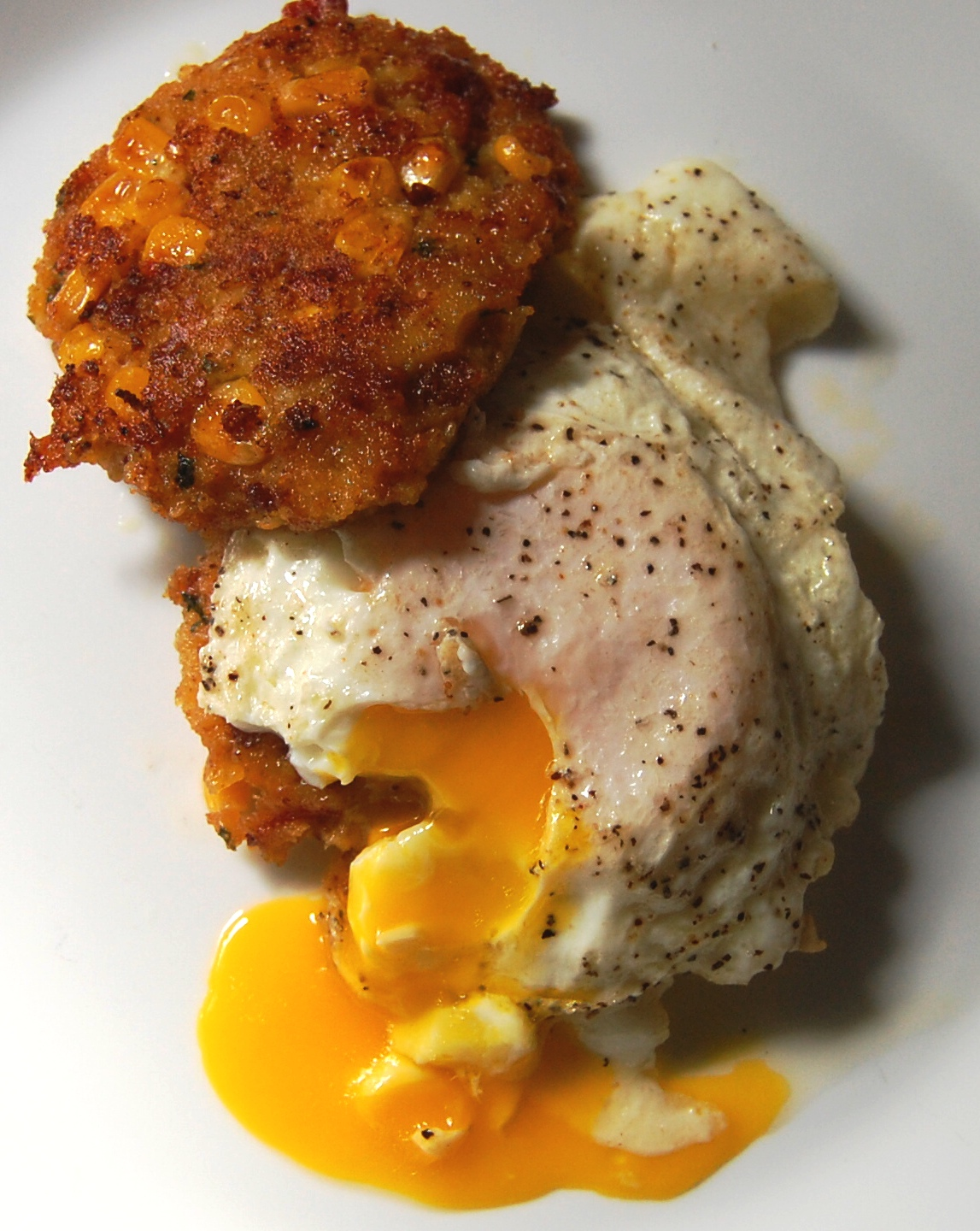 Bacon and cheddar cornbread cakes with fried eggs .