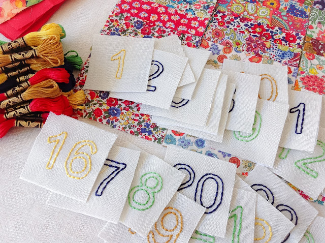 Hand-embroidered numbers advent calendar pockets