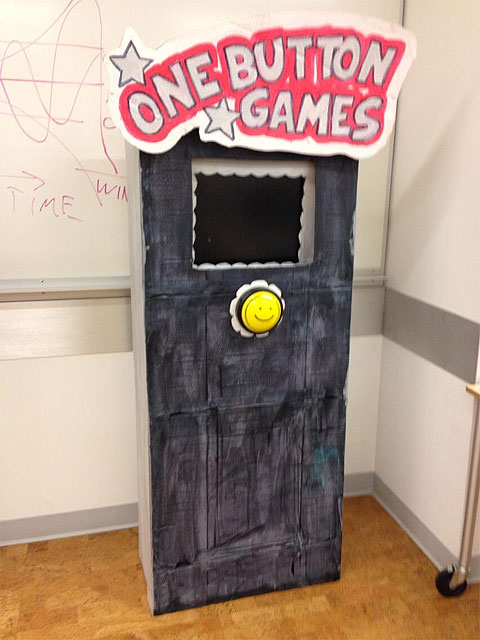 One Button Games cardboard arcade cabinet with smiley yellow switch.