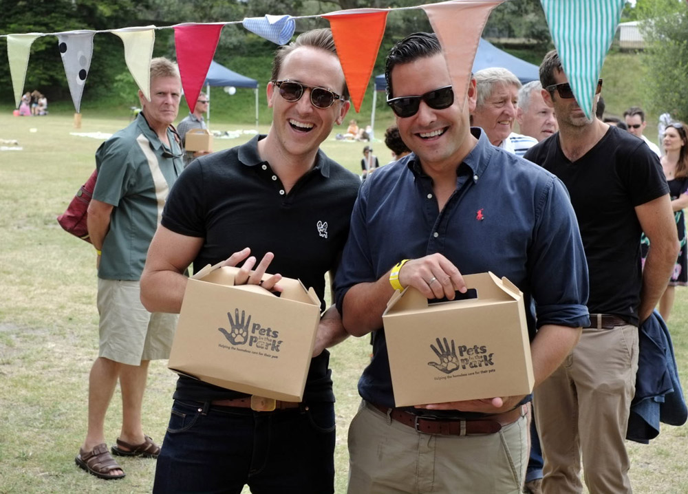 Alex Greenwich and friend with picnic lunch boxes for Pets In The Park Gala Picnic, Centennial Park Sydney. Photographed by Unique Event Photography Sydney.