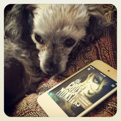 Murchie halfway cringes away from a white iPod touch with the cover art for Dreams of Gods & Monsters on its screen. The cover shows a portrait of a pale skinned woman wearing dark, heavy eyeliner. Golden antlers hover in front of her face. The title is displayed across the image on a slant.