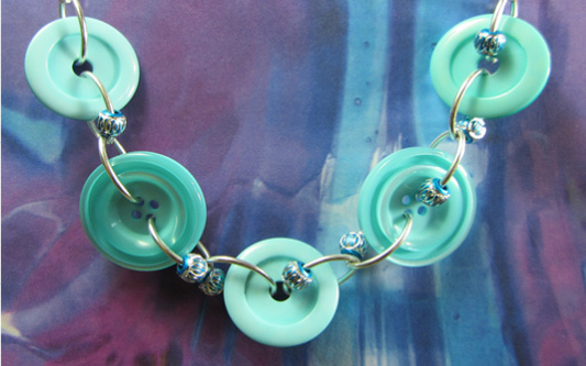 Necklace has big teal buttons and small accent beads floating on silver loops
