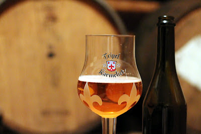 Hoppy Golden Solera with barrels in the background.