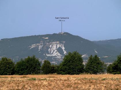 L'església de Sant Sebastià, damunt de Santa Eulàlia de Riuprimer, vista des de la Serra de Sant Marc