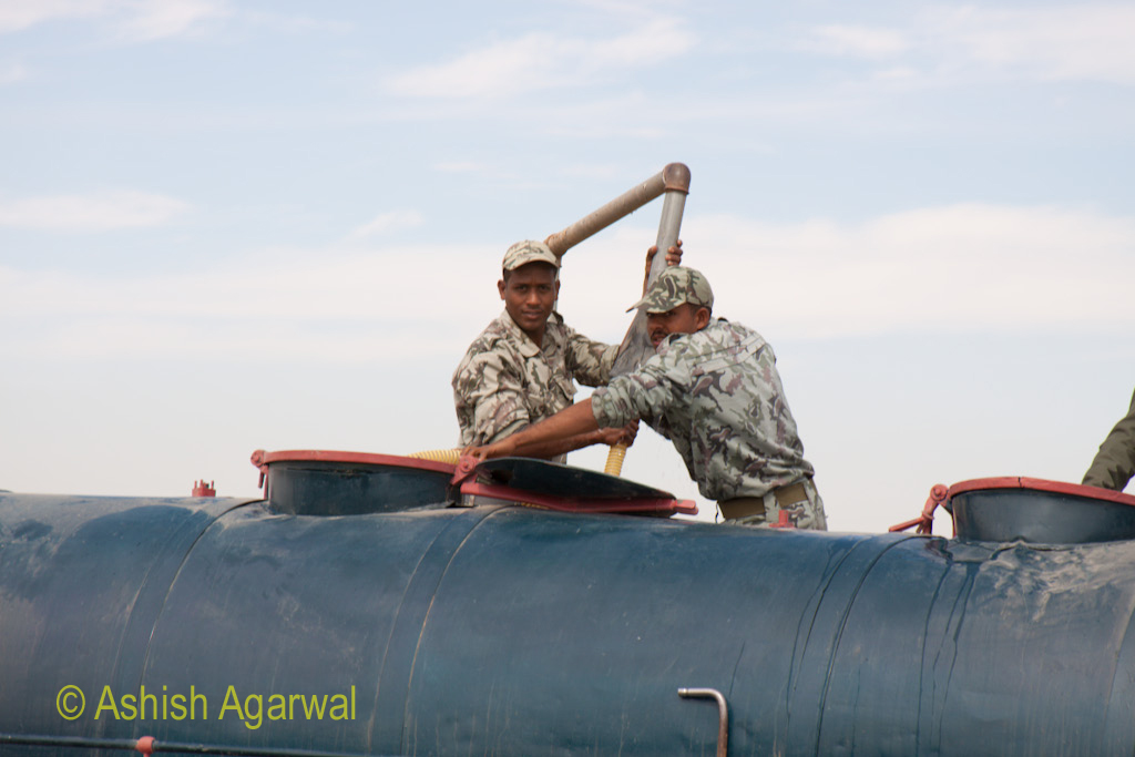 Egyptian army soldiers filling a tanker with water at a middle point