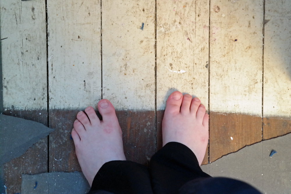 Bare feet on bare floorboards