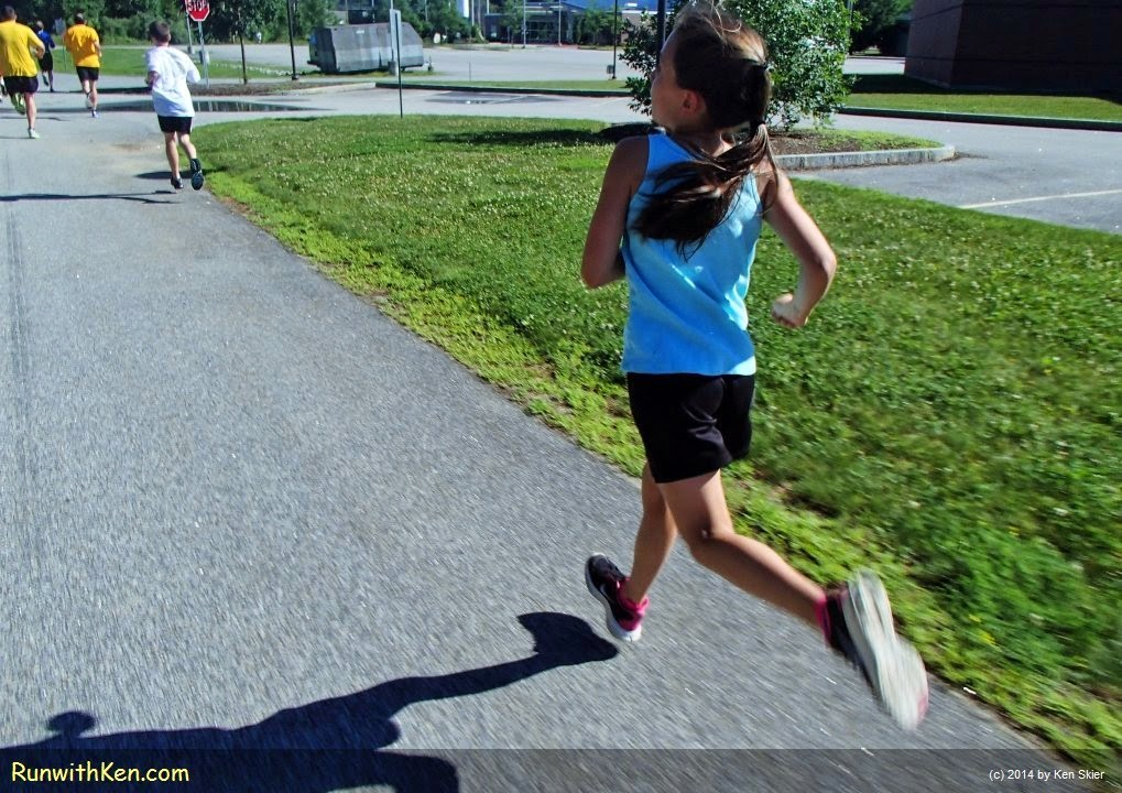 Dramatic action photo of a young runner FLYING down the road at the 4K on the 4th Trail Race, at NHTI in Concord, MA. Sports photography by Ken Skier aka