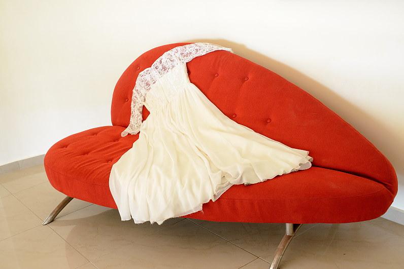 graikiška vestuvinė suknelė ant raudonos širdies formos sofos