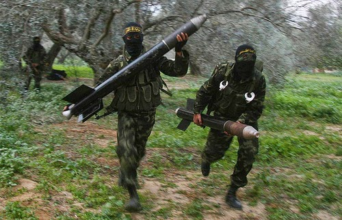 Masked Palestinian militants from Islamic Jihad run with homemade rockets on the outskirts of Gaza City  to put in place before later firing them into Israel - January, 2009.