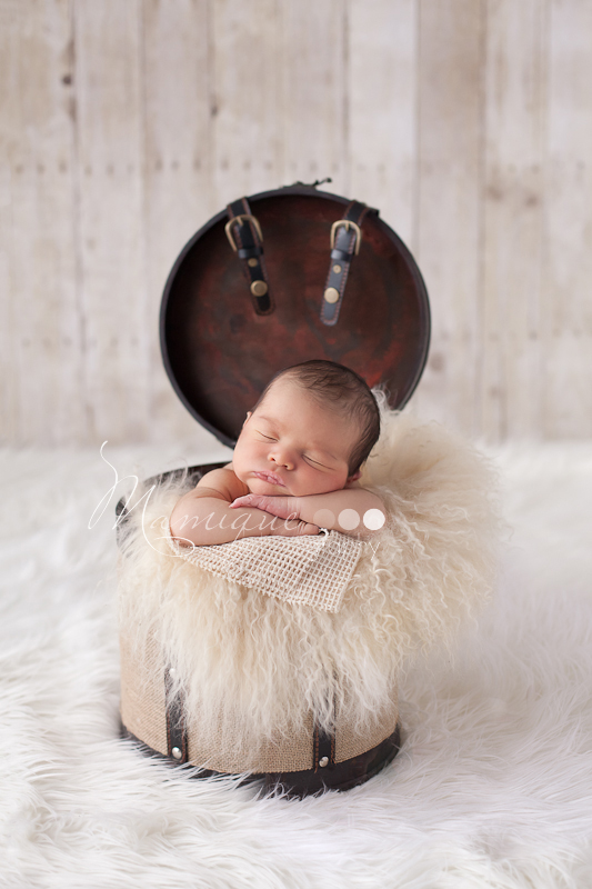Cute baby in bucket on cream curly fur