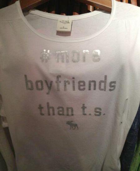 """Tulisan pada baju yang mempersendakan  Taylor Swift - """"#more boyfriends than t.s."""""""
