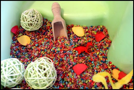 rainbow rice, dinosaurs and scoops for sensory play