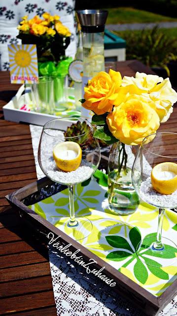 Dekorierter Terrassentisch im Sommer mit Zitronenkerze und frischer Zitronenlimonade