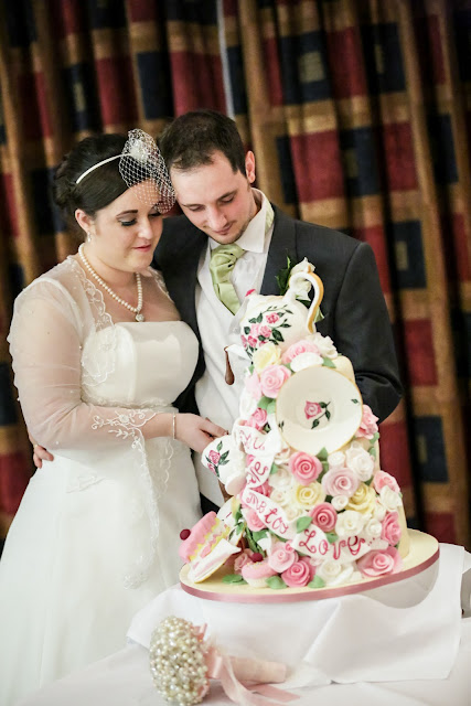 bride and groom cutting cake from Epic Cakes floral 3d tea party cake