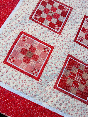 an up close picture of the quilting details on a red and white quilt
