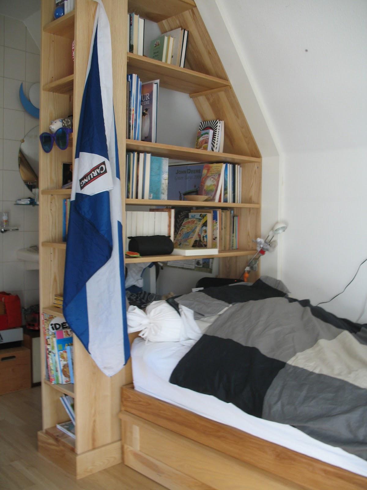 een bed en een boekenkast voor een jongenskamer essenhout geolied de slaapkamer ligt onder de kap waardoor de wanden vanaf 140 m hoogte de kamer binnen