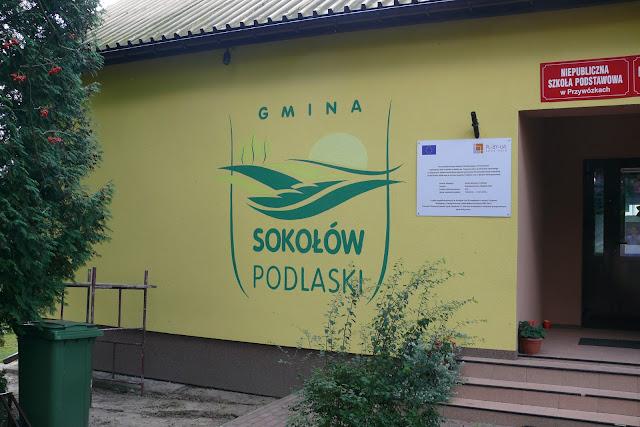Ręczne malowanie loga na ścianie, malowanie pędzelkiem loga na zewnętrznej elewacji budynku