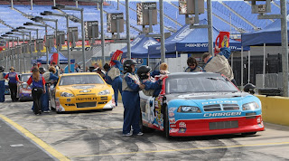 The Richard Petty Ride-Along racecars on the track.