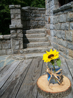 A sunflower sits in a jar in front of a stone staircase.