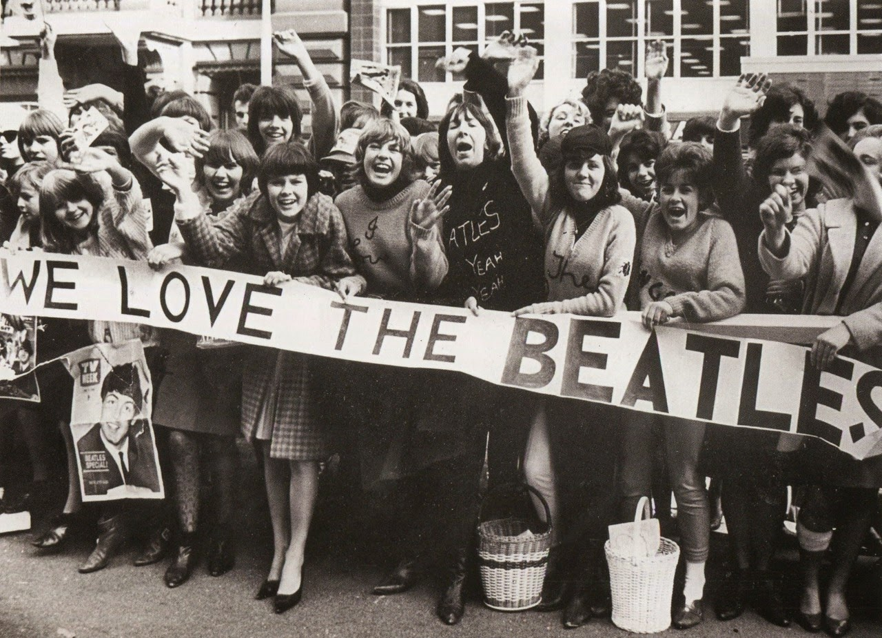 Screaming Beatles Fans Holding Banners And Waving At Band