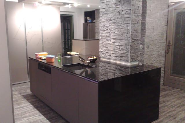 Cuisine moderne avec grand ilot et mur d'armoires avec façades sans poignées. Plan de travail noir poli brillant