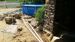 Drainage pipe now in place underneath, trench partially filled in and the flow and return pipes connected up to the pool
