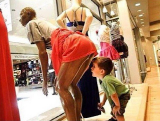 funny picture: child looks at the bottom of a display mannequin