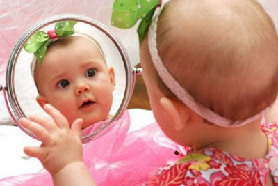 Image of cute little baby girl looking mirror