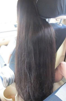 Young college girl with loose long hair inside a car.